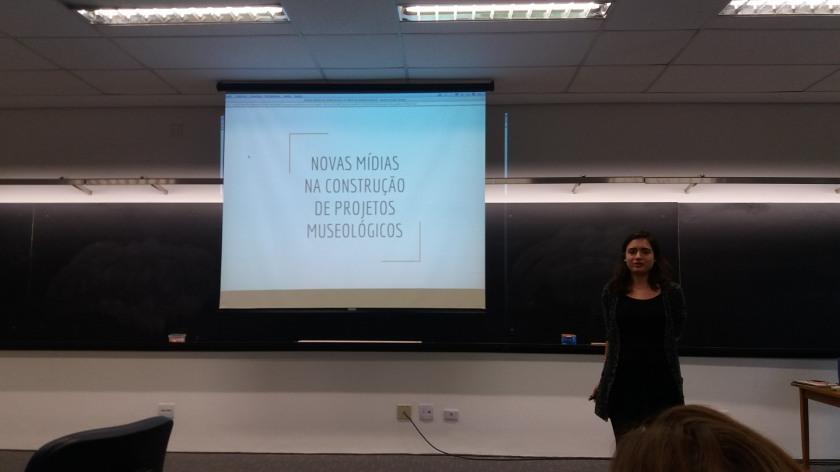 """Giovanna está em pé, em frente a uma lousa digital, onde está um slide com o título de seu projeto: """"novas mídias na construção de projeto museológicos"""""""